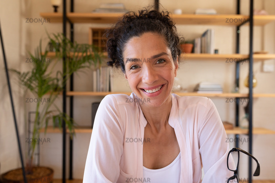Portrait of smiling caucasian woman sitting at desk, working from home