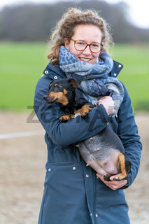 A smiling young woman holds a pregnant Jack russel terier in her arms. The dog's big belly can be seen clearly. Outside in the winter. Selective focus on dog