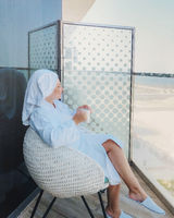 Woman in white bathrobe and towel on head sitting on armchair with cup of coffee on balcony