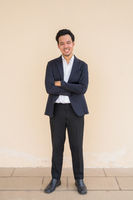 Full length portrait of Asian businessman wearing suit against plain background with arms crossed while smiling