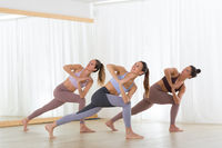Group of young sporty attractive women practicing yoga lesson with instructor in modern bright yoga studio.
