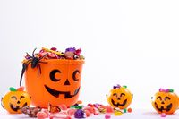 Composition of halloween bucket with trick or treat sweets, spider and pumpkins on white background