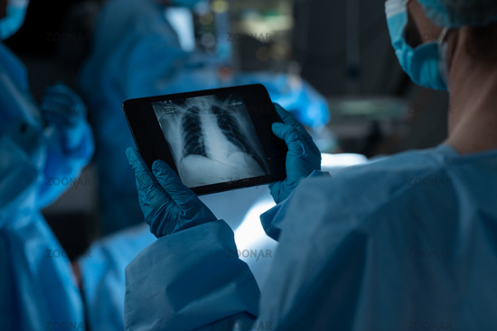 Mixed race surgeon in operating theatre wearing face masks looking at lung x-ray on tablet