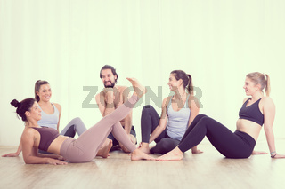 Group of young sporty attractive people in yoga studio, relaxing and socializing after hot yoga class. Healthy active lifestyle, working out in gym.