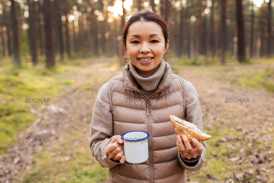 woman with mushrooms drinks tea and eats in forest