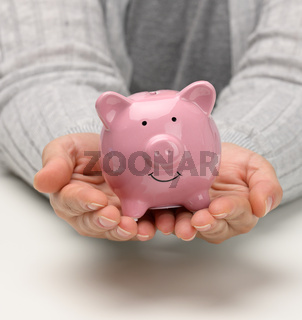 female hands are holding a pink ceramic piggy bank. Accumulation concept, budget control