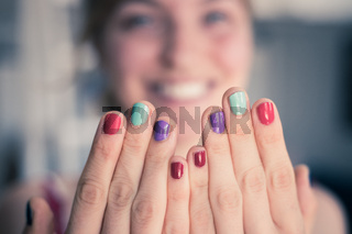 Pretty young woman with colorful nail polish. Smiling face in the blurry background.