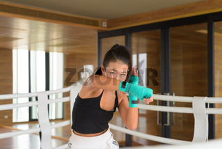 Asian woman kick boxer shadow boxing at gym boxing ring