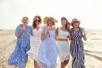 Cheerful women with wine walking on beach