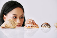 Beautiful african american woman looking on different seashells on white background.