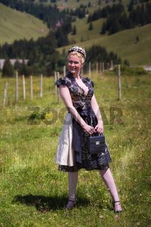 Blonde Frau im schwarzen Dirndl mit Tasche