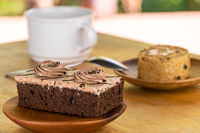 Mini chocolate cream sponge cake in wooden plate and piece of prune sponge cake in wooden dish with a cup of coffee.