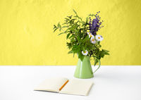 notebook with pencil and bunch of flowers in jug