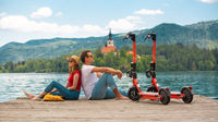Young couple using electric scooter as modern ecological mean of transport while exploring green country Slovenia at vacations. Green eco energy concept with zero emission. Warm sunshine filter.
