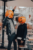 Guy and girl with pumpkin heads look at each other