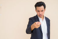 Portrait of Asian businessman wearing suit against plain background and pointing finger at camera