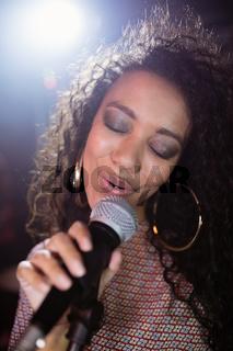 Female singer with eyes closed performing at nightclub