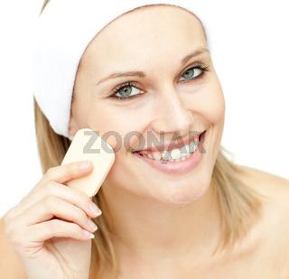 Cheerful woman putting foundation cream