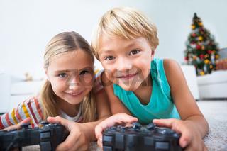 Happy siblings playing video games on floor