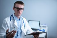 Young male doctor consults patient in hospital office, holding medical examinations in hands. General practitioner in white medical coat looks into camera and makes an appointment with patient online