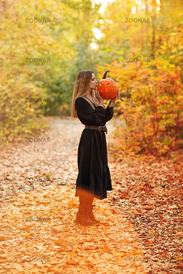 Young blonde female holding scary crafted pumpkin in front of her face