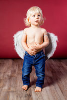 Infant baby with angel wings and jeans