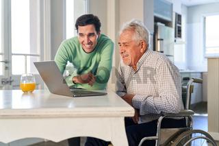 Neugieriger Senior und junger Mann am Laptop Computer