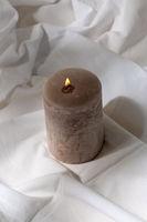 burning aroma candle on white sheet