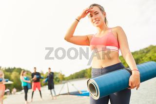 Sportliche junge Frau als Coach mit Yogamatte
