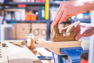 Home handyman using a plane for smoothing down a piece of timber