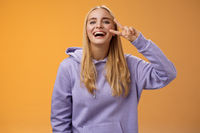 Attractive friendly carefree millennial blond girl in purple hoodie having fun friends laughing joyfully show peace victory hippie sign adore perfect chilly spring weather, orange background
