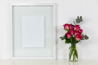 View of a picture frame, with pink roses placed in a glass vase on plain white background