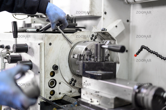 Close up view of worker operating a high precision turning operation on a multi axis lathe, CNC machine tool.