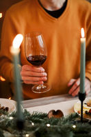 Man in orange sweater holding glass of red wine while celebrating Christmas with family at home
