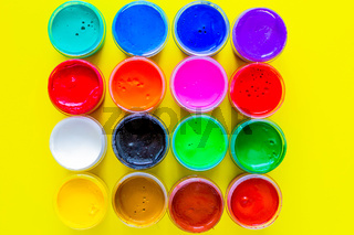Many bright cans of paint stand together on a yellow background close-up. top view, flat lay, copy space, isolate.