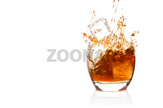 Ice cube falling into glass of whisky