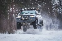 SUV jumped on rise of snow winter forest