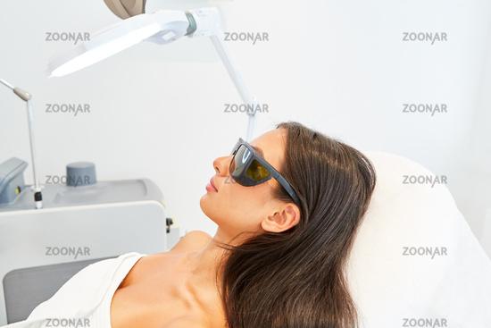 Patientin mit Schutzbrille in der Schönheitsklinik