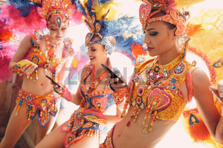 Woman in brazilian samba carnival costume with colorful feathers plumage with mobile phone in old entrance with big window