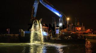 Baggerschiff arbeitet in der Nacht