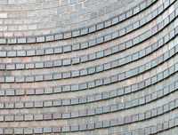 close up of a curved grey brick wall with raised rows forming a pattern