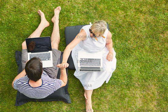Paar sitzt Hand in Hand im Garten am Computer