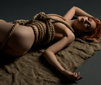 Nude woman tied with rope view