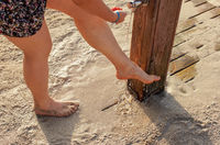 Young woman removing sand form her legs under beach shower near sandy ground, water drops spraying over feet