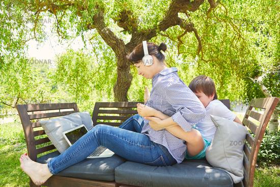 Mutter am Laptop PC wird von Kind bei Arbeit gestört
