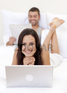 Beautiful woman using a laptop and man reading a newspaper