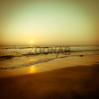 Beautiful sunset at tropical beach. Ocean sandy coast under evening sun. South India landscape in vintage style