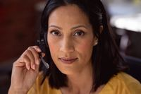 Portrait of happy caucasian businesswoman wearing phone headset sitting at desk smiling to camera