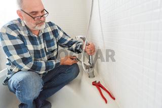 Klempner montiert oder repariert Brauseschlauch