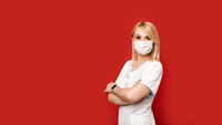 Confident female doctor wearing protective face mask standing on red background arms crossed. Young woman intern in medical clothes posing.
